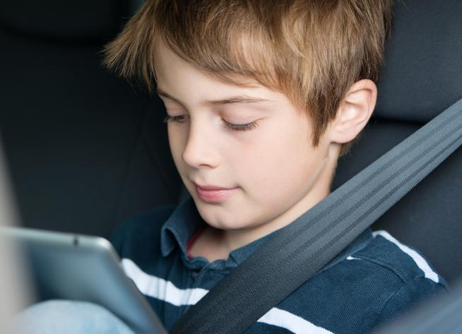 Boy in car with iPad