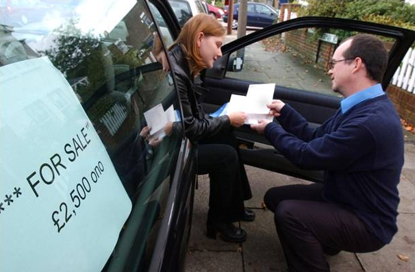Second-hand car buyer checking paperwork