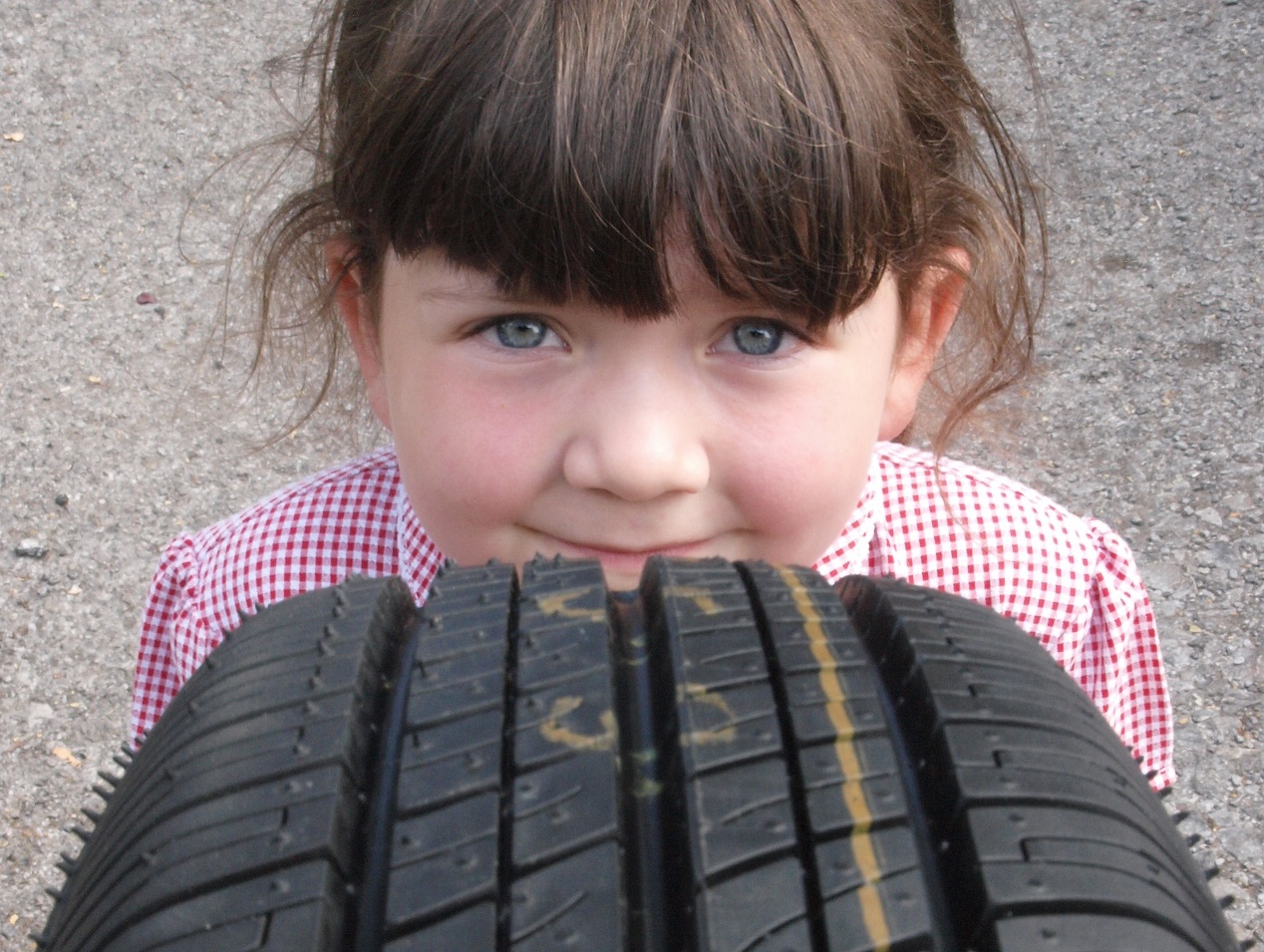 Child inspecting tyre